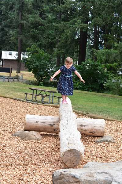 PMG PHOTO: EMILY LINDSTRAND - Children can climb across logs in a new play area at Timber Park.