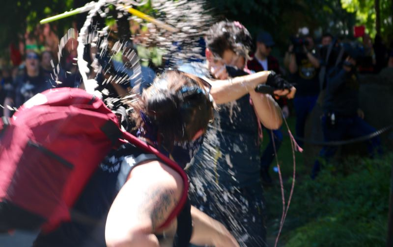PMG PHOTO: ZANE SPARLING - A woman hurls liquid on prominent live-streamer Andy Ngo during a downtown Portland protest on Saturday, June 29.