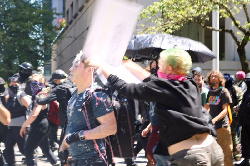 PMG PHOTO: ZANE SPARLING - A person hits Andy Ngo with a sign during a political protest in downtown Portland on Saturday, June 29. , Portland Tribune - News Ted Wheeler's adviser offers support to Andy Ngo, but says no 'physical evidence' of quick-drying cement Milkshake protest stirs up controversy across U.S.