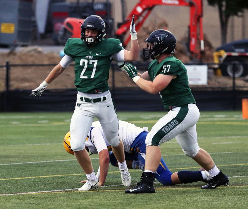 PMG PHOTO: DAN BROOD - Fletcher Ahl (27) celebrates with teammate Carter Dennis after getting a quarterback sack for the Tigers in their early-season win over Barlow.