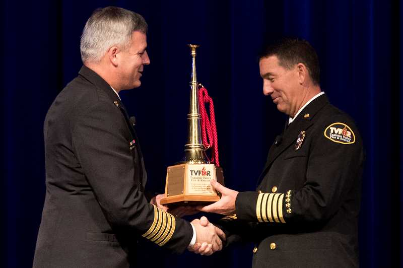 TIMES PHOTO: JAIME VALDEZ - TVF&R Chief Mike Duyck presents the symbolic transfer of command to new chief Deric Weiss during a ceremony held Monday at Rolling Hills Community Church in Tualatin.