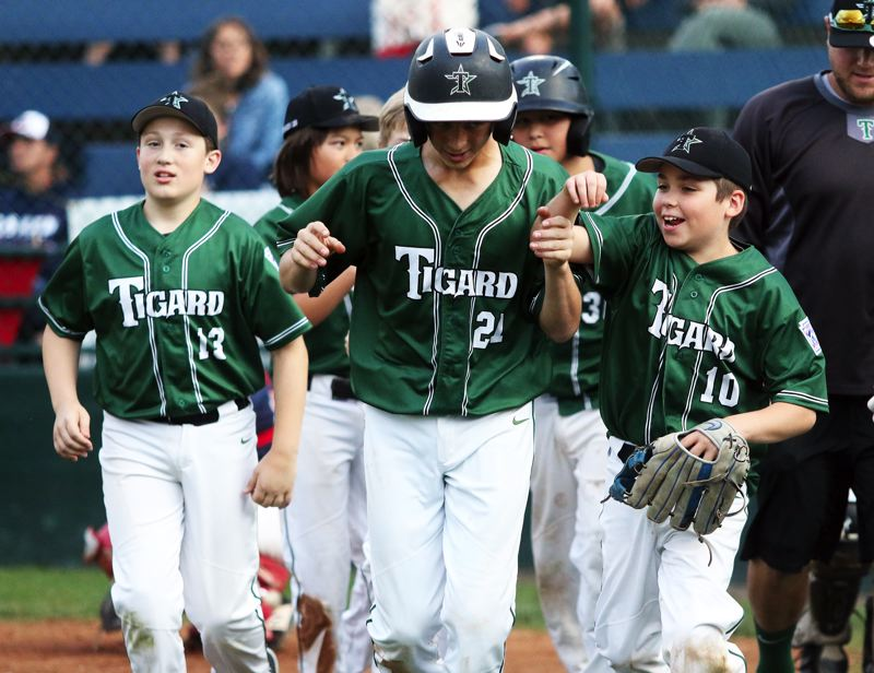 PMG PHOTO: DAN BROOD - Tigard's Miles Ott (center) is greeted by his teammates, including Michael Harms (left) and Lando DuChene (10) following his two-run home run in the 12-2 win over Lake Oswego.