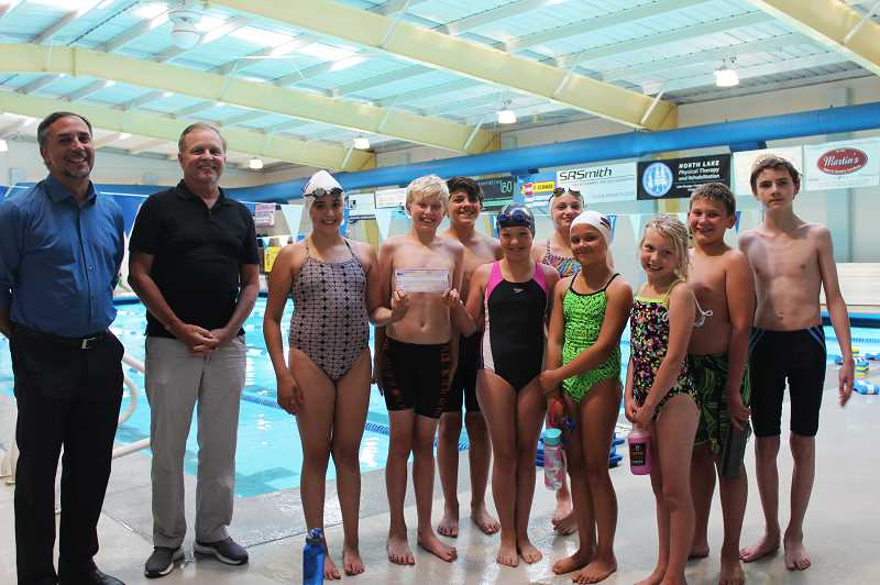 PMG PHOTO: KRISTEN WOHLERS - On Monday, July 1, swim club members present the check for $841 from their plant sale to Canby Center Director Ray Keen (left) and Canby Superintendent Trip Goodall for the Suicide Prevention Task Force.