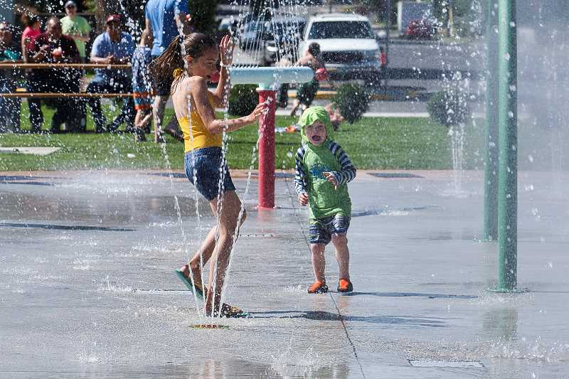PHOTO BY JASON BLACKMAN - Youths splash through one of the pressure changing sprinklers.