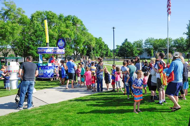 PHOTO BY TOM BROWN - Kids wait in line with their parents for a free snow cone.