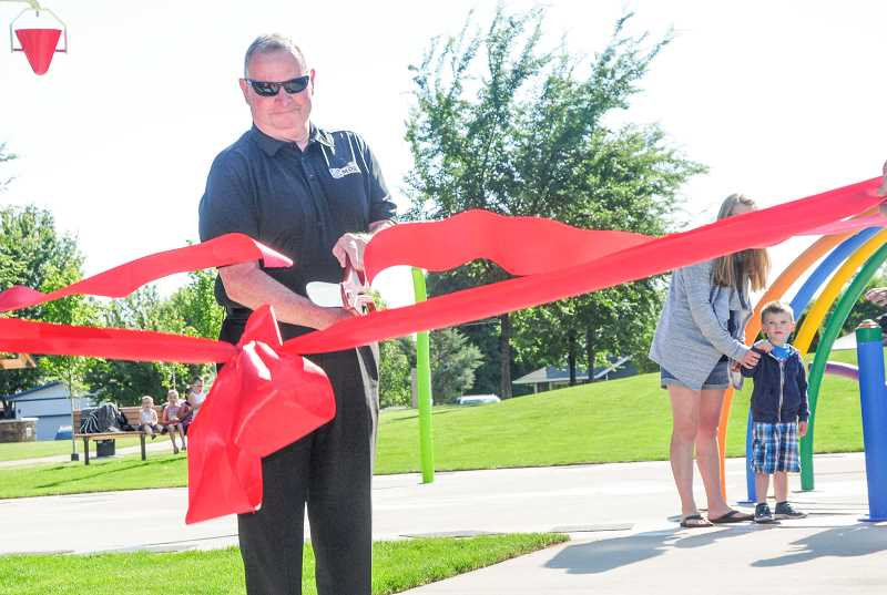 PHOTO BY TOM BROWN - Mayor Richard Ladeby gets things started ribbon-cutting before the Stovall family hits the button to get the water going.