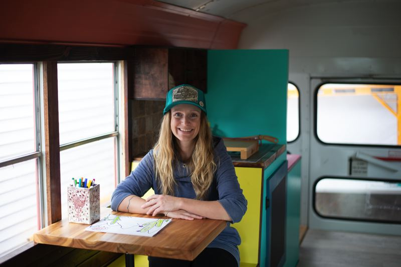 PMG PHOTO: ANNA DEL SAVIO - Jenna Reineking, one of two founders of Tumblewheel Studios, sits in the nonprofits renovated bus. Reineking and her husband, Nick Patton, take the bus to schools, festivals and community organizations, where they host free art classes.