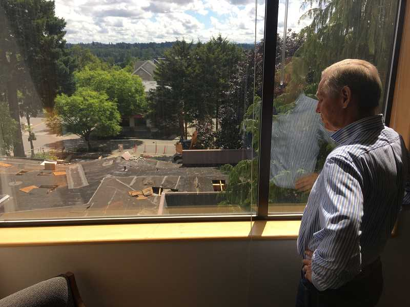 PMG PHOTO: SAM STITES - Former City Manager Scott Lazenby, who retired July 1, looks out on the demolition at the site of the new City Hall — a project he helped usher in — from his office window