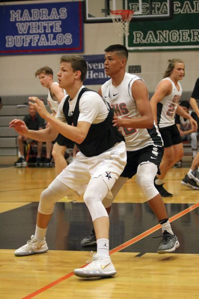PMG PHOTO: JIM BESEDA - Clackamas' Ben Gregg (left) looks to get the ball as Gladstone's Jude Ashpole brings defensive pressure during a recent summer game at Gladstone High School.