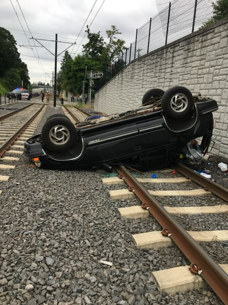 COURTESY PHOTO - Train traffic was disrupted in Milwaukie on Friday, July 5, after a car tumbled off an embankment wall.