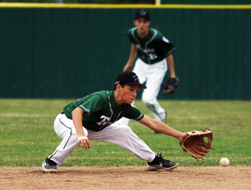 PMG PHOTO: DAN BROOD - Tigard Little League Majors shortstop Dominic Taylor reaches out to field a ground ball during the first inning of the team's District 4 tournament semifinal game with Raleigh Hills.