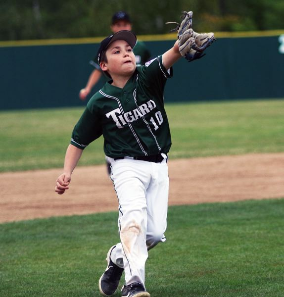 PMG PHOTO: DAN BROOD - Tigard Little League third baseman Landon DuChene fields the ball during the first inning of the team's District 4 tournament semifinal game with Raleigh Hills.