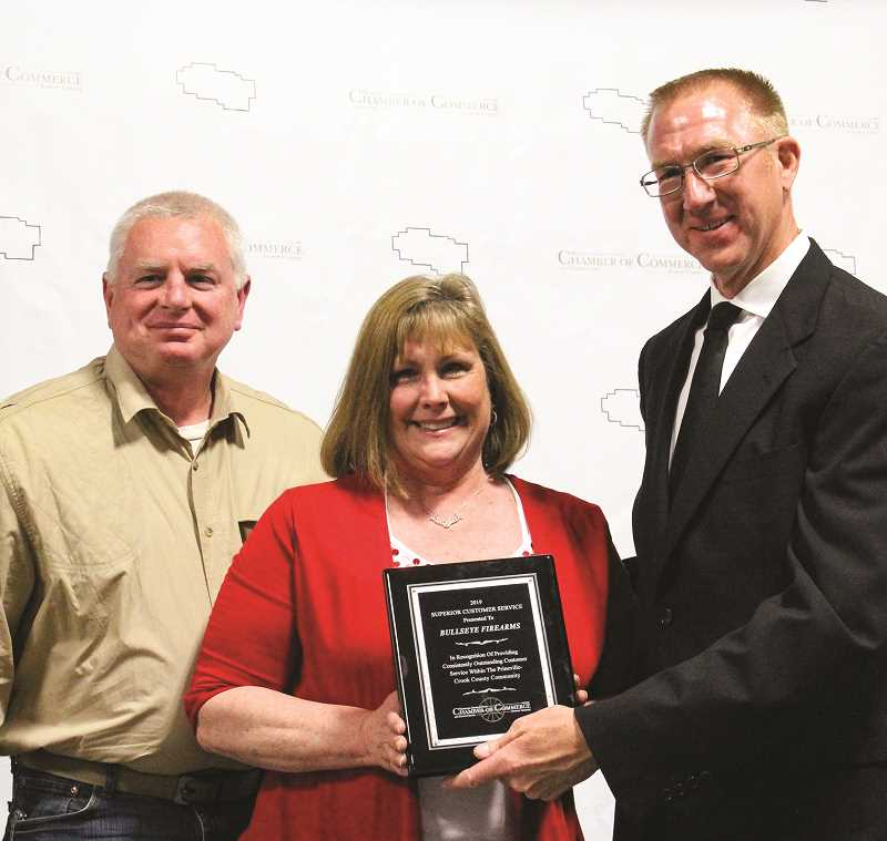 CENTRAL OREGONIAN - Chamber board member Casey Kaiser presented the Superior Customer Service Award to Bullseye Firearms owners Bill and Lissa Remington at the 2018 Chamber's Masquerade Gala and Awards Dinner, held this past April.