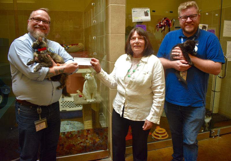 PMG PHOTO: MATT DEBOW - Friends of Multnomah County Shelter Animals President Karol Dietrich presents a $10,000 check to Wade Sadler, Multnomah County Animal Services interim director of animal services, while holding a kitten at the shelter. The shelters communications coordinator Jay LeVitre also poses with a young feline.
