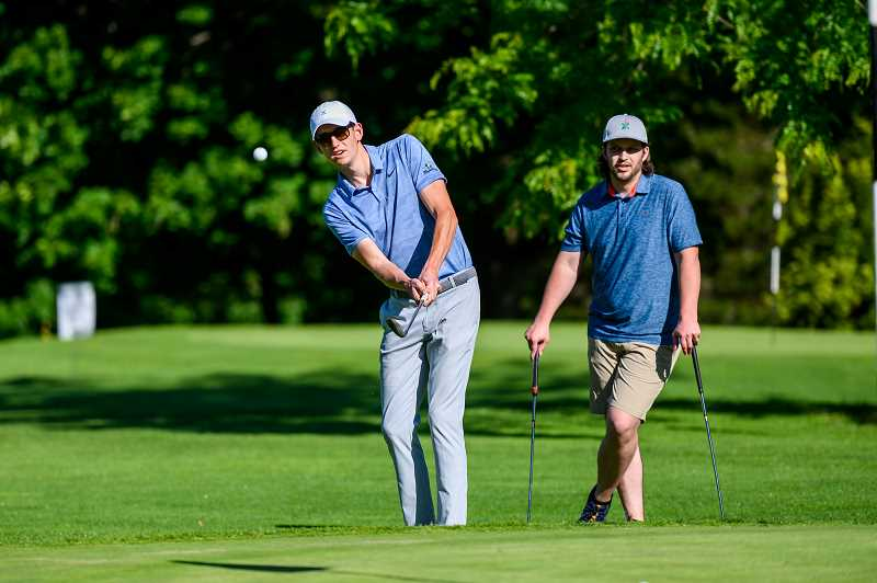 COURTESY PHOTO: EVERGREEN EVENT PHOTOGRAPHY - Mitch Mellen (right) looks on as Anthony Garbarino (left) chips a shot onto the 17th green at the LO Public Golf Course for a chance at birdie.