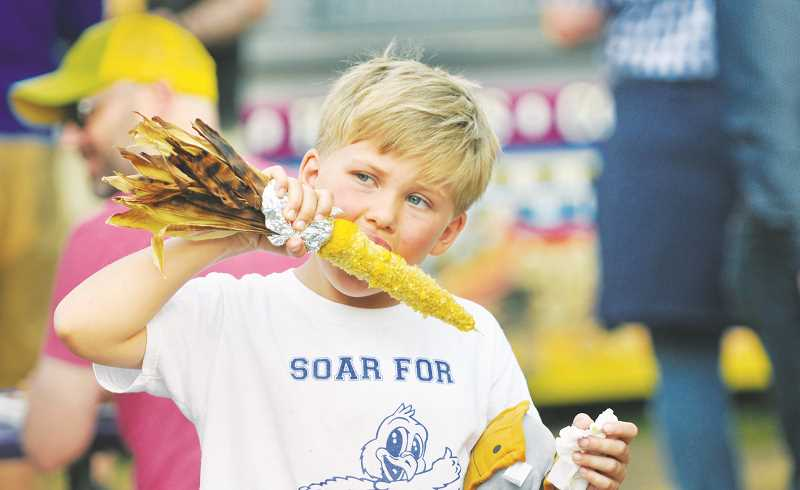 GRAPHIC PHOTO: GARY ALLEN - A youngster enjoys a tasty treat purchased in the midway Friday evening at the St. Paul Rodeo.