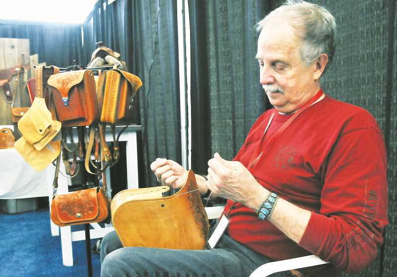 GRAPHIC PHOTO: GARY ALLEN - Monty Mickelson of Pale Rider Maker crafts a leather good at his booth at the Wild West Art Show on Friday evening.