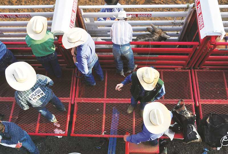 GRAPHIC PHOTO: GARY ALLEN - Competitors and others gather behind the chutes in preparation for the bull-riding competition Friday evening.