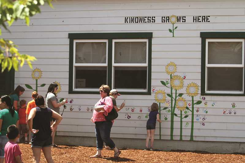 PMG PHOTO: PHIL HAWKINS - Students and community members painted colored hand prints on the walls at Gervais Elementary School on June 26, decorating a new garden space that will be completed before the start of the 2019-20 school year.