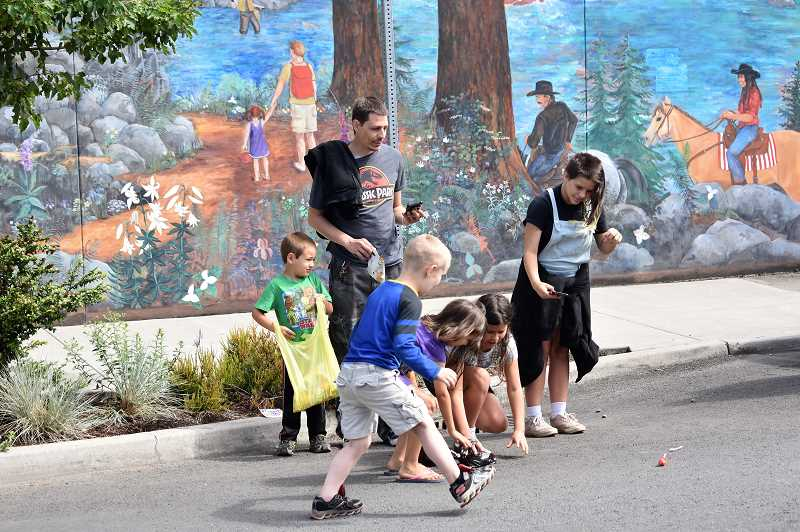 PMG PHOTO: EMILY LINDSTRAND - Children delightfully scramble for candy during Estacadas 2019 Fourth of July parade.