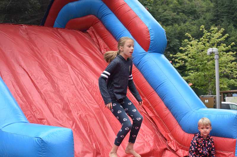 PMG PHOTO: EMILY LINDSTRAND - Children jump in a bounce house during DJ Jonny Blaze's third annual River Fest last weekend.