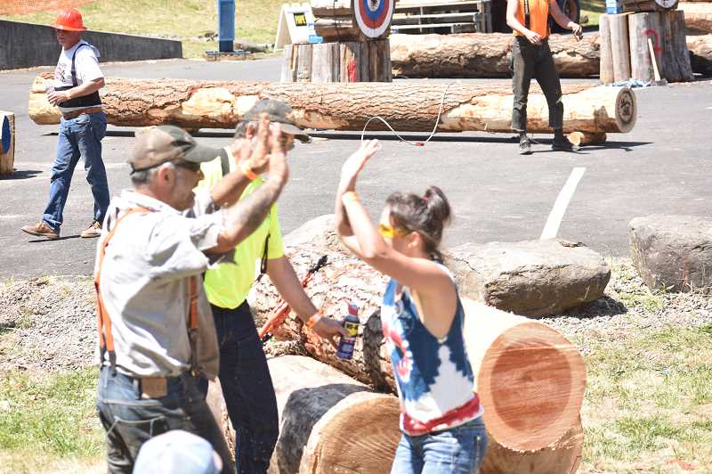 PMG PHOTO: EMILY LINDSTRAND - Participants in the Estacada Timber Festival's jack and jill competition are triumphant after winning the event.