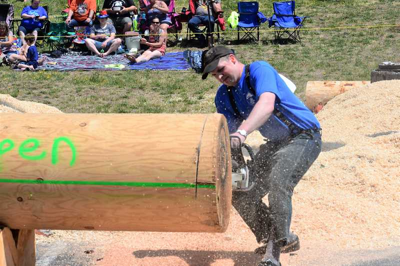 PMG PHOTO: EMILY LINDSTRAND - A competitor races to cut through a log during the Estacada Timber Festival on Thursday, July 4.