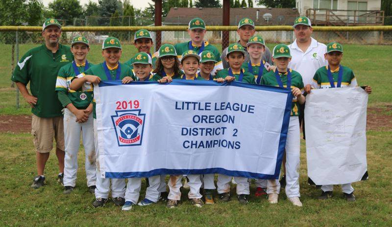 PMG PHOTO: JIM BESEDA - Clackamas Little League Majors team members (left to right) coach Chris Stephen, Zavier Alvarez, Coco Nita, Greyson Smith, Adam Ruiz, Benny Bowen, Brian Ostrin, Jace Eveland, Cole Althen, Ben Stephen, Jack Gibbon, assistant Everett Mayers, Jayden Mayers, assistant Chris Althen, and Nick Brighouse pose in front of their championship banner after Tuesdays 14-11 victory.