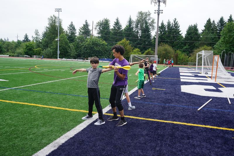 PMG PHOTO: CLAIRE HOLLEY - A Lake Oswego High School student athlete helps the young campers learn how to properly throw a javelin.