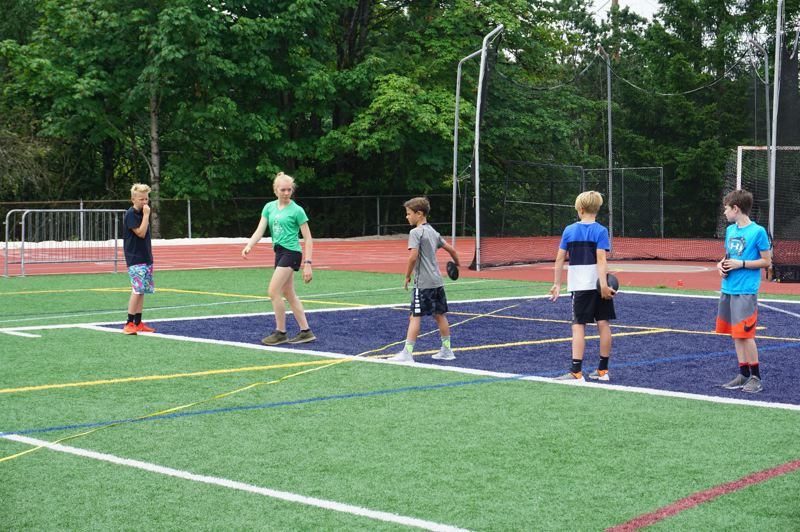 PMG PHOTO: CLAIRE HOLLEY - Campers learn how to throw discus on the LOHS field.