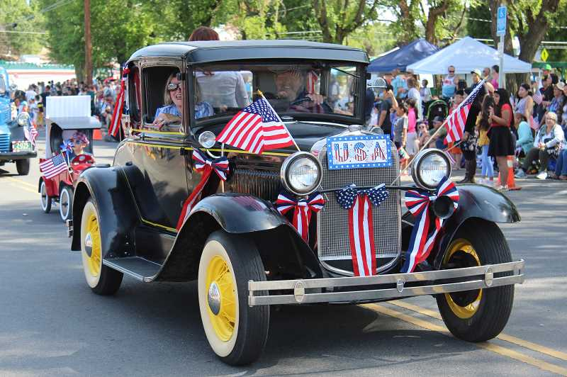 HOLLY M. GILL/MADRAS PIONEER - Marian and Jon Granby sport flags and bows on their 1930 Model A Ford entered in the parade, which had more than 100 entries this year, a record number.