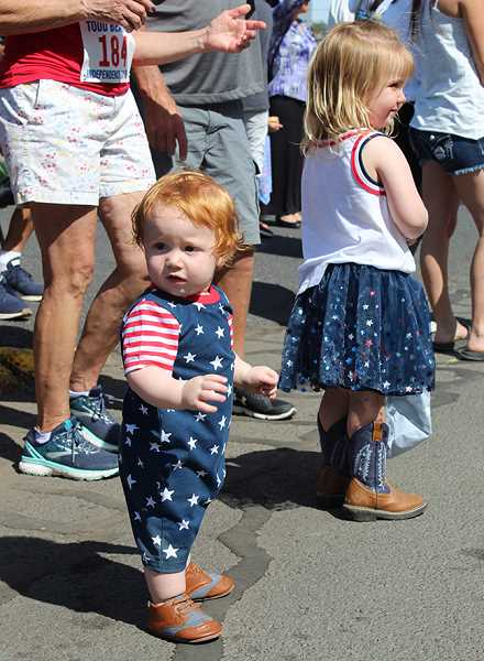 HOLLY M. GILL/MADRAS PIONEER - Lawrence Doughty, 1, and his sister, Natalie Doughty, 2, take in the sights and sounds of a Fourth of July parade, while nearby their parents, Raelea and Britt, and Mavrik, Lawrence's twin brother, enjoy the parade, as well.