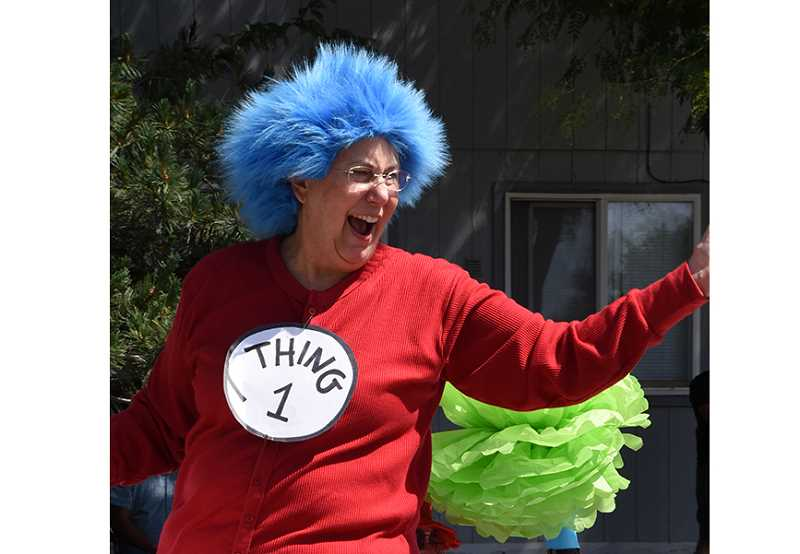 PHOTO BY BILL VOLLMER - Margee O'Brien, dressed as Thing 1 from the Seuss book, 'The Cat in the Hat,' rides with the Relay For Life group during the July 4 parade.