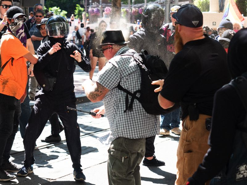 PMG PHOTO: KIT MACAVOY - A man is sprayed with chemicals during a brawl near Pioneer Courthouse Square on June 29 in Portland.