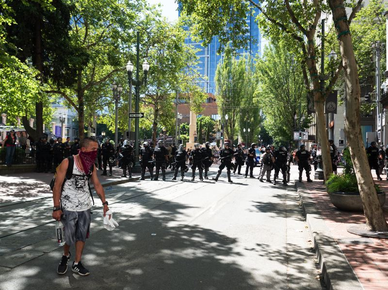 PMG PHOTO: KIT MACAVOY - A protester stands near a Portland Police Bureau riot officers skirmish line on June 29.