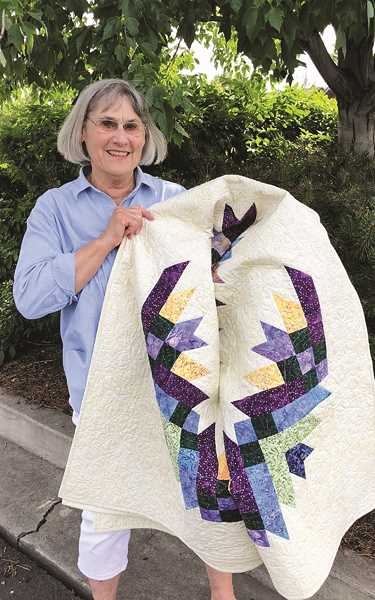 PHOTO COURTESY OF TERRY HAGEN - June Isaak won the raffle quilt at the Crook county Quilt Guild's 22nd Biennial Country Quilt Show held late last month in the Pioneer School gym.