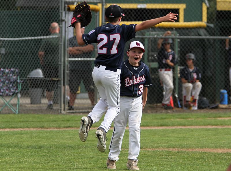 PMG PHOTO: MILES VANCE - Lake Oswego first baseman Reid Stanton leaps into the air while pitcher Ben Robertson smiles at the conclusion of their team's 11-2 state championship win over Bend North at Riverside Park in Clackamas on Thursday, July 11.