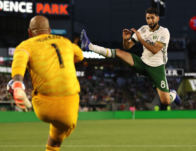 PMG PHOTO: JAIME VALDEZ - Portland Timbers midfielder Diego Valeri jumps towards the ball kicked by Colorado Rapids goalkeeper Tim Howard in the first half Saturday night at Providence Park.