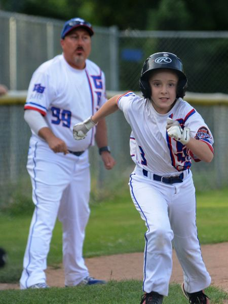 PMG PHOTO: DAVID BALL - Greshams Gavin Messer dashes for home, while manager Chris Rounds watches in the background.