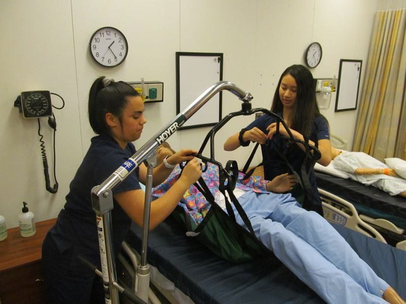 PHOTO BY SETH GORDON - Alena Decoito, left, and Sandra Srey demonstrate how to use a Hoyer Lift to transfer a patient from a hospital bed to a chair.