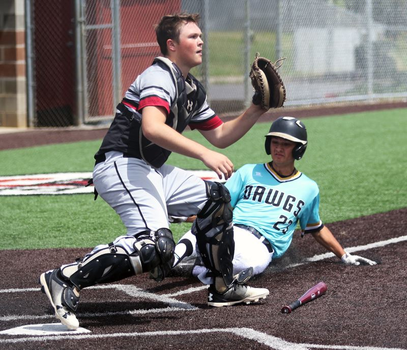 PMG PHOTO: DAN BROOD - Tualatin's Shawn Christensen (right) slides home safely while Sherwood catcher Kade Emmons awaits a throw during Thursday's game at the Clackamas Diamond Classic. Tualatin got a 9-5 victory.