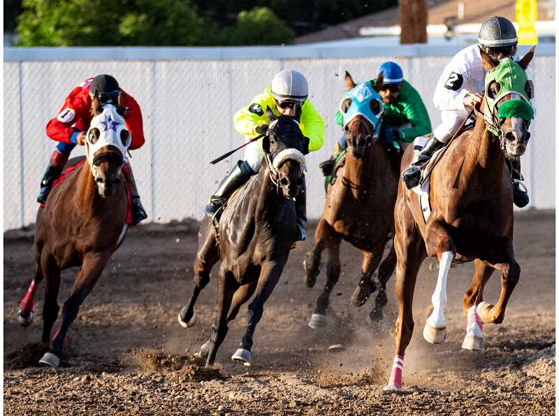 LON AUSTIN/CENTRAL OREGONIAN - Horses round the final corner during Friday's five furlong second race. The two horse, far right, ridden by Taylor Smith, won the race, while Hot and Sassy, ridden by Jake Samuels, middle in yellow silks, finished second.