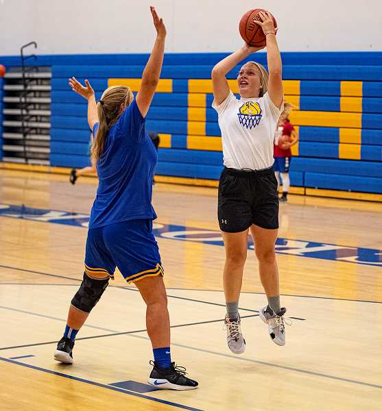 LON AUSTIN/CENTRAL OREGONIAN - Josie Kasberger shoots over Emma Bales last Friday during the final day of the Cowgirls basketball camp. The camp was run by Ryan McCarthy, a CCHS graduate, who is now the head women's basketball coach at University of Alaska Anchorage.