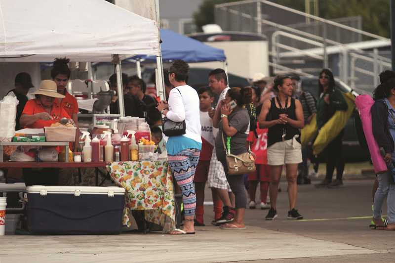 PMG PHOTO: PHIL HAWKINS - Food vendors set up on the concrete pad between fields at Woodburn High School, providing guests with a variety of local cuisine options.