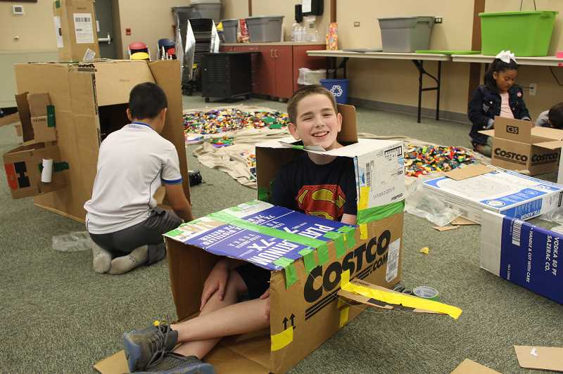 PMG PHOTO: KRISTEN WOHLERS - Michael Vedder, who is visiting from out of state, builds a kid-sized spacecraft at Molalla Public Library on July 10.