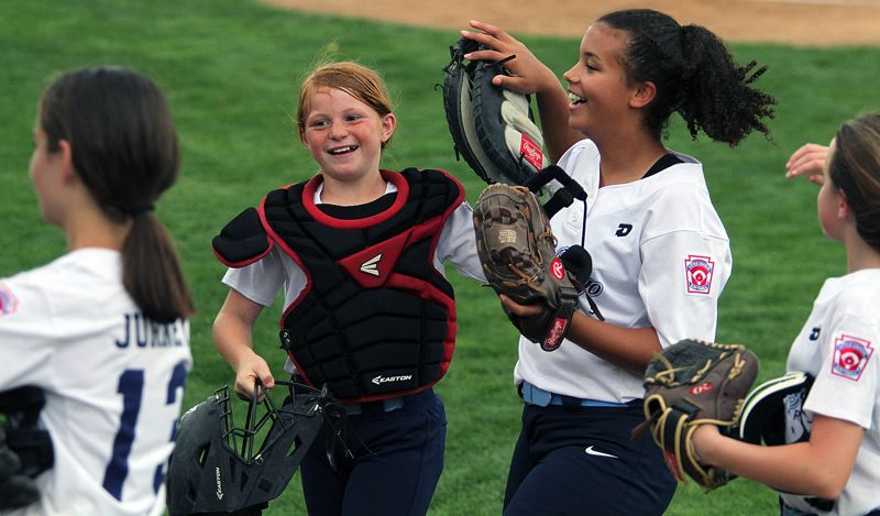 PMG PHOTO: MILES VANCE - Lake Oswego's Kate Stingle (center) and Braelynn Jenkins celebrate an out during their team's 18-8 win over Forest Grove in the Distict 4 Majors tournament at Alpenrose Dairy on Tuesday, July 16.