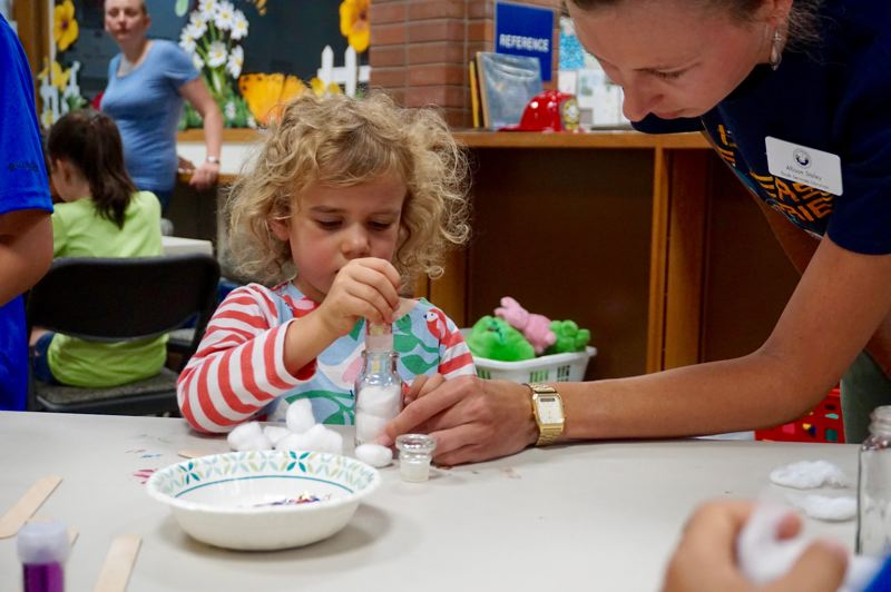 PMG PHOTO: CLAIRE HOLLEY - Youth Services Librarian Allison Staley helps Lucy Singer-Brown create her galaxy jar.