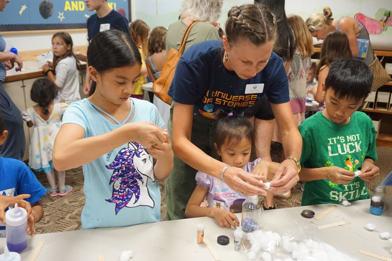 PMG PHOTO: CLAIRE HOLLEY - Staley helps summer readers with their galaxy jars.