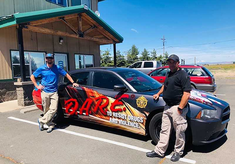 SUBMITTED PHOTO - Brandon Searcy, left, hands the car back over to Kevin o'Brein, the school resource and D.A.R.E. officer, right, after finishing up the wrap job.