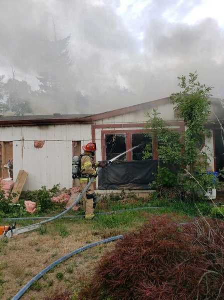 COURTESY PHOTO: MOLALLA FIRE - Molalla Fire finishes putting out the flames at a Macksburg Road fire on Wednesday evening, July 17.